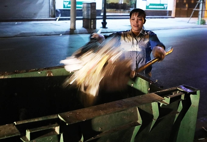 Ha puts her trash trailer every day from 5 p.m. to collect trash on several streets in Hai Ba Trung District. The 35-year-old environmental worker works until midnight when the city garbage truck passes her route, she follows and dumps the collected trash on their container. When trash from the truck leaks on the street, she collects it and puts it in the public bins.Environmental workers like Ha don't question the late night requirement of their work. Only at that time, the citizens will not feel bothered.When work finishes at 3 a.m., Ha returns to her small home on Linh Nam Street, 8 km away. She also takes on a part-time position at a sewing factory, fetching an additional one million dong ($43) that helps her get by.