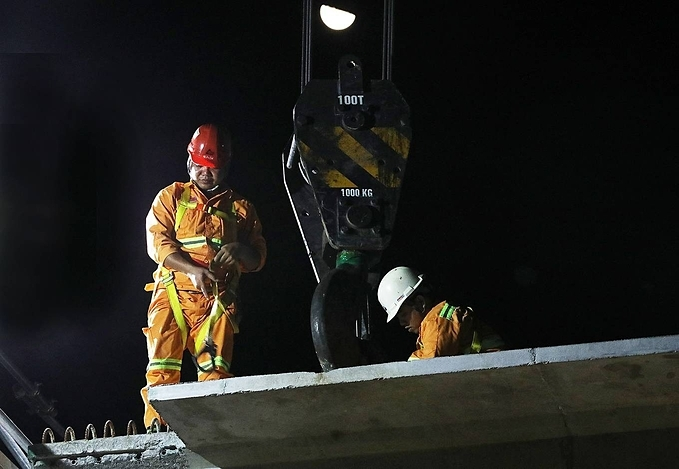 Nguyen Ba Su (left), a technical worker checks the winch hook used to lift the beams at a suspended bridge construction in Cau Giay District at 1 a.m. Construction team works overnight, when traffic participation is the lowest.