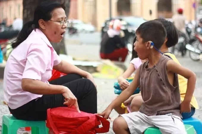 A mother communicates with her deaf son as she takes him to a hospital in Hanoi for a health check. Photo by VnExpress/Duc Thanh.