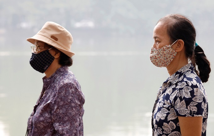Vietnamese women wear protective masks while walking around Hoan Kiem Lake in Hanoi, Vietnam, as the air quality continues to be unhealthy, October 2, 2019. Photo by Reuters/Kham.