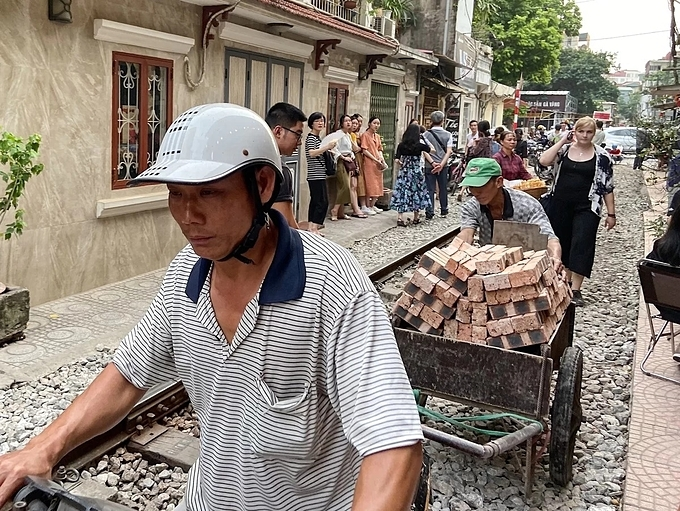 Although it looks dangerous, locals have made full use of the track and the little space along it for daily activities and livelihood, sparking curiosity from foreign tourists. After appearing more than a few times on international sites and travel blogs, the rail has become an attraction.