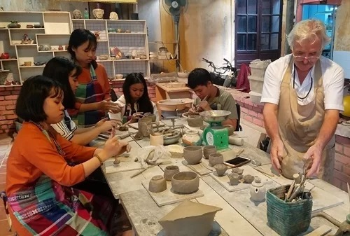 Oliver guides disabled children in Hope's Center the art of Raku Pottery making. Photo by VnExpress/Vo Thach.