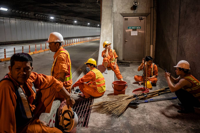 A group of workers takes a break near the gate to the tunnel at 2 in the morning.The job is hardest in rainy days because of all the mud, said a worker named Nguyen Thi Bich Hanh, part of the cleanup group.