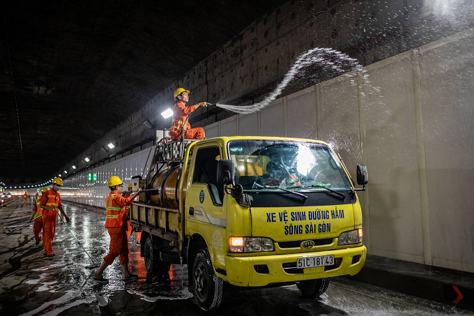 A group of around 20 workers clean the road surface and the panels that help reflect light inside the tunnel.What people normally see is dense traffic every day through this tunnel.  What they don't see are us workers who are here every night, working until almost 4 a.m. when the tunnel reopens to traffic. Without regular cleaning, the tunnel would be really dirty because of all the dust, soil and sand falling from the trucks, said Nguyen Thai Uy, who was spraying water on the panels.