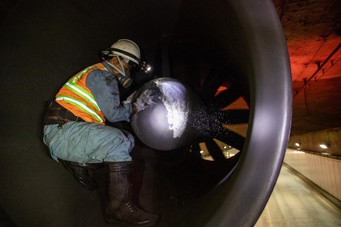 Engineer Hoa wears protective clothing and a gas mask as he cleans a turbine. I've been doing this job for two months now. It has become normal to me. What bothers me most is all the dust and the fact I have to stay at a high point, so I need to be equipped with all the safety tools.