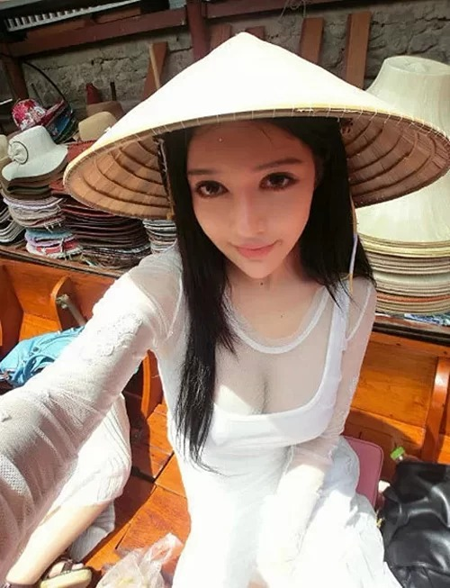 Zhang Wan You,  a famous showgirl in the Chinese gaming industry, wearing ao dai with a deep V-neck exposing large areas of her breasts.