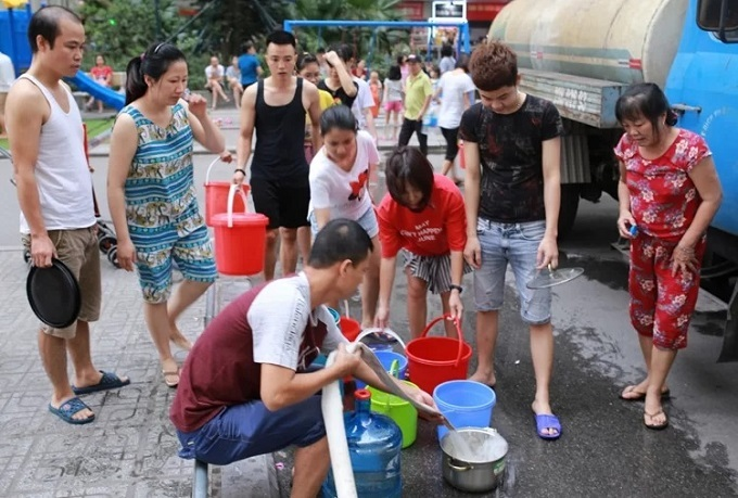 Residents at a condo in Hoang Mai District gather to get clean water from a tank truck. Photo by VnExpress/Vo Hai