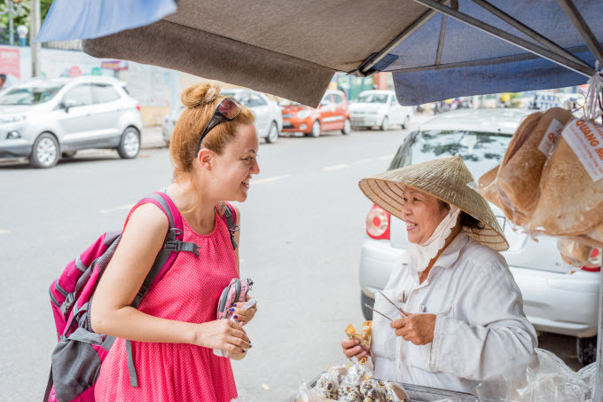 A female foreign tourist talks to a street vendor in the central beach town of Nha Trang. Photo by Shutterstock/An Nguyen.