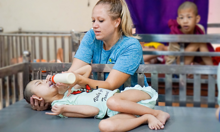 Carly taking care of a child. Photo by VnExpress/Trong Nghia.