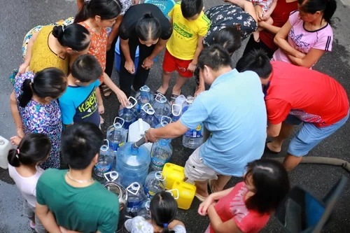 People queue up to fill water from trucks. Photo by VnExpress/Tat Dinh.