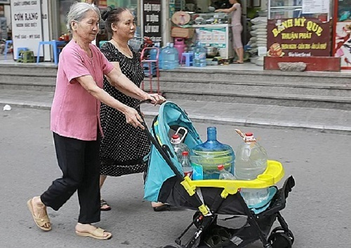 Residents at Linh Dam Urban Zone carry water in a baby stroller. Photo by VnExpress/Tat Dinh.