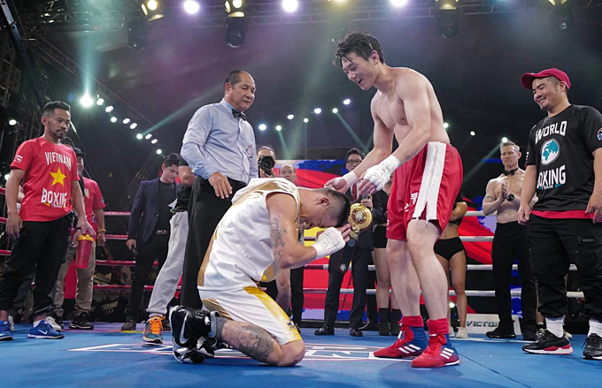 Hoang bows before his opponent with respect as the referee announces him as the winner after 10 rounds.