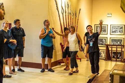 A tour guide introduces the exhibition's artifacts and explains the art of Tuong to foreign tourists.