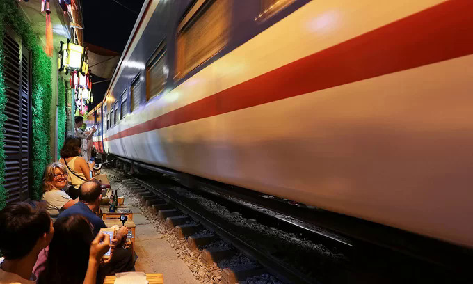 Foreign tourists use smartphones to capture the moment when the train passes by. Photo by VnExpress/Giang Huy.