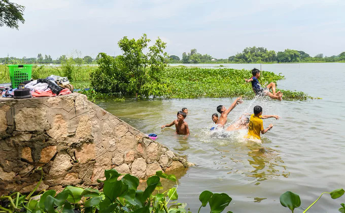 Cham ethnic children play in Bung Binh Thien Lake, one of the largest freshwater lakes in the Mekong Delta.Many activities of the local people such as fishing, bathing, washing and playing     take place around the lake.