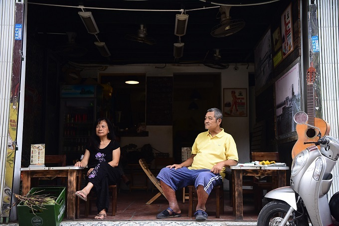 Mai and Dung sits in their coffee shop open in front of their house on the Train Street. Photo by VnExpress/Giang Huy