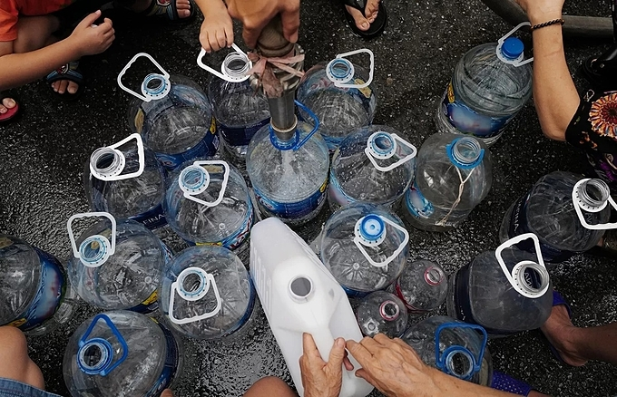 Residents at an apartment project in Hanoi gather their water bottles to get free clean water from a tank provided by the city on October 14, 2019. Photo by VnExpress/Ngoc Thanh