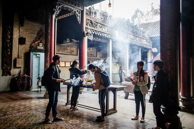 A group of students burn incense near the open yard, which besides allowing natural light also lets the smoke out of the pagoda.According to the management board, the place is usually crowded on holidays, New Year and full moon days or the Goddess Thien Hau worship day on the 23rd of the third lunar month.