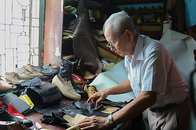 Ngoc works on a piece of crocodile leather. Photo by VnExpress/Hoang Huy.