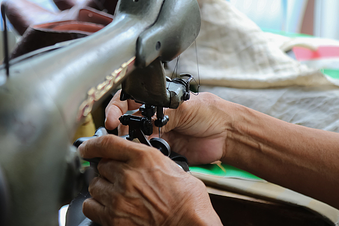 Ngoc works on his old sewing machine. Photo by VnExpress/Hoang Huy.