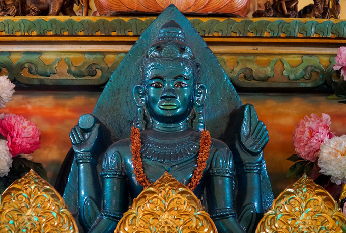 In the middle is a sitting Vishnu idol made of stone by the Cham ethnic people around the 15th century. This Vishnu idol, 1.5 m high and weighing nearly one ton, was found in anearby tree hollowand brought to the pagoda. Since then it has also been called the Four Handed Buddha Pagoda.