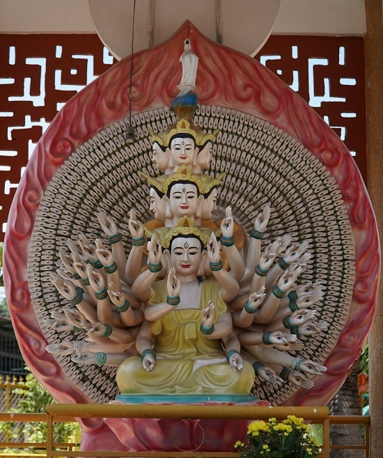 An idol of the 1,000-eyed, 1,000-armed Avalokitesvara sitting on a lotus in the pagodas courtyard.
