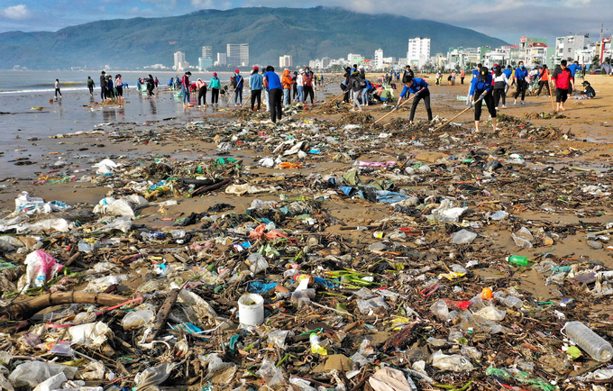 Over 500 students and locals of Quy Nhon walk along the beach to collect trash like nylon bags, twigs or nets on Friday after storm Matmo made landfall on Wednesday. A 4-km section of the beach is filled with trash.