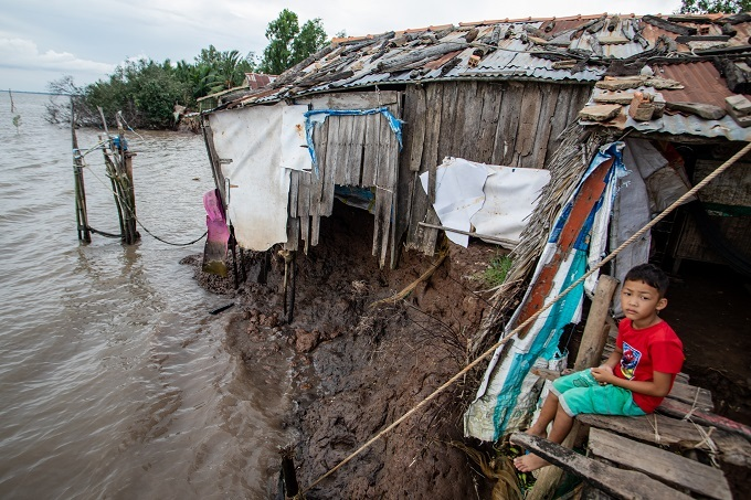 A boy sits at his house that has partly collapsed into the river due to erosion in Soc Trang Province, southern Vietnam, July 2019. Photo by VnExpress/Thanh Nguyen.