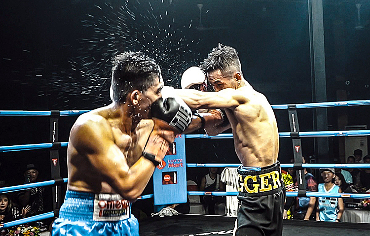 Tran Van Thao (R) strike a punch towards Filipino boxer Ponciana Remandiman. Photo by VnExpress/Dong Huyen.