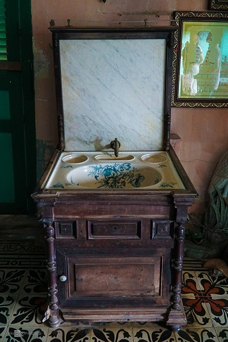 A flower-patterned sink with a wooden base.