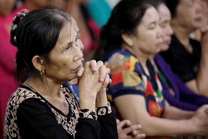 Catholics attend a mass prayer for 39 people found dead in the back of a truck near London, in Nghe An Province, Vietnam. Photo by Reuters.
