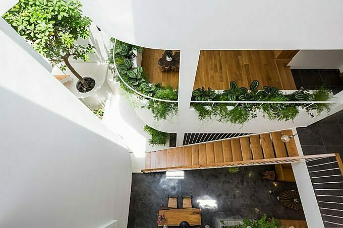 The rooms are linked with each other by wooden bridges. The owner uses a lot of trees and plants to fill the space with green. The atrium floods the interior with sunlight, which also enters the rooms through the large windows.