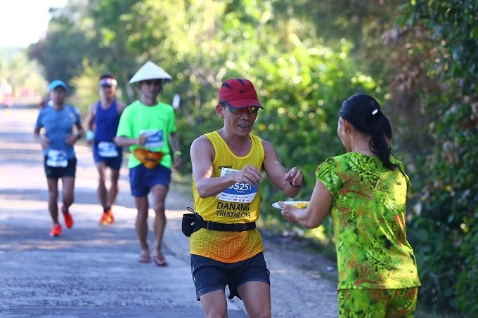 A local woman (R) offers mango to runners at VnExpress Marathon in Quy Nhon, central Vietnam, June 9, 2019. Photo courtesy of VnExpress Marathon.