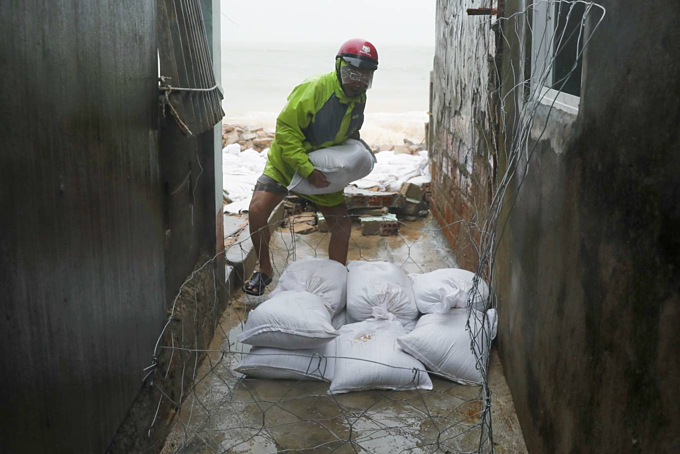 Nguyen Van Khanh, 56, uses sand bags to block the waves from crashing into the neighborhood.My house is further inside, but we still have to use sand bags to block [the waves] for peace of mind, he said.