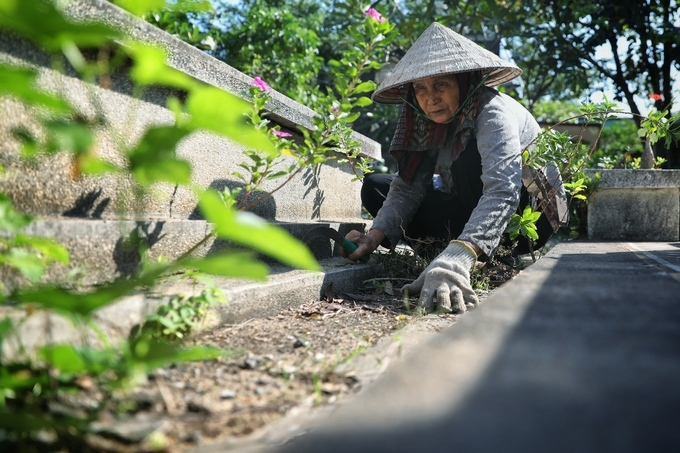 Huong cuts the grass. Photo by VnExpress/Diep Phan.