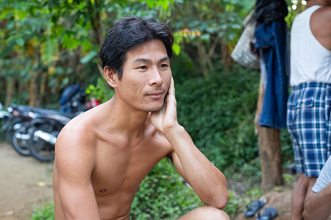 Duong, 33 takes a break and shoots the breeze with his nudist fellows after his swim in the Red River, November 6, 2019. Photo by Chris Humphrey