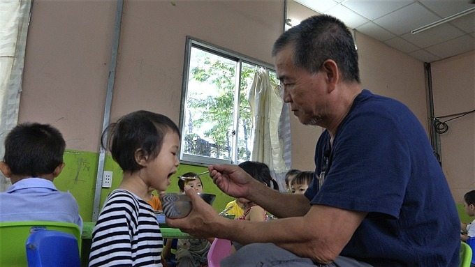 Hiep feeds one of his children. Photo by VnExpress/Minh Nhat.
