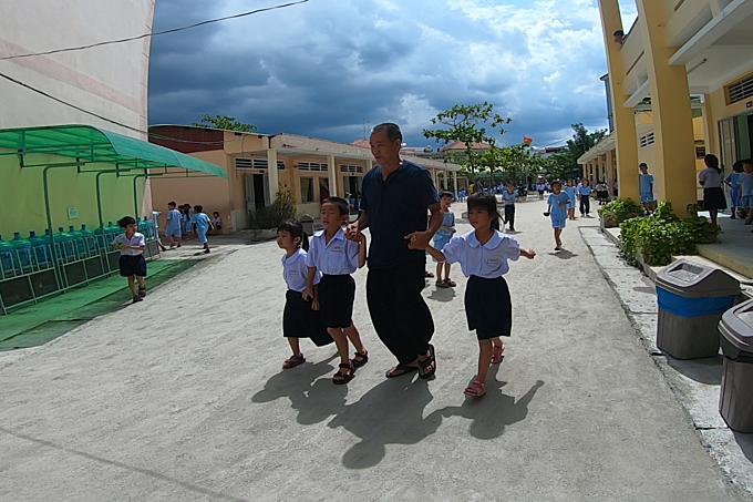 Hiep picks up his children. Photo by VnExpress/Minh Nhat.