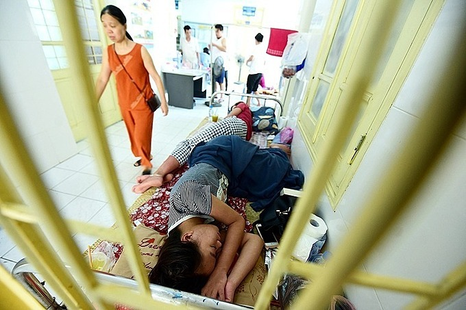 Two patients share a bed put along the hallway of a hospital in Hanoi in 2017. Photo by VnExpress/Giang Huy