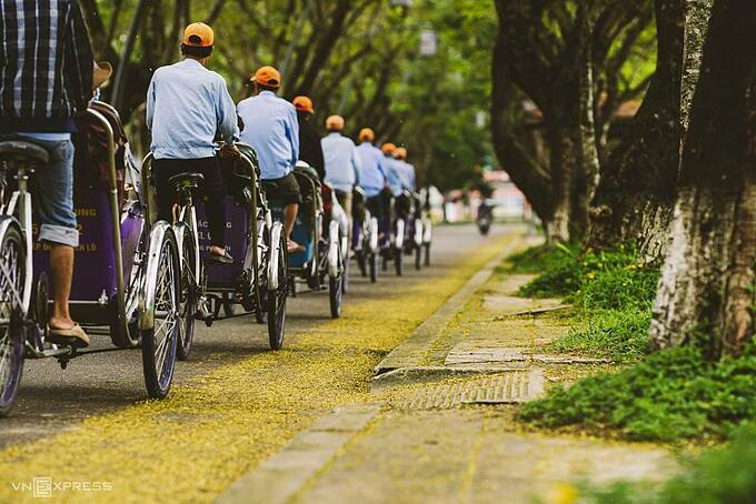 A cyclo entourage on 23/8 Street.Photographer Kelvin Long from Hue hopes visitors feel enchanted by the fall color of Hue just as he does. On early mornings or early afternoons, riding the small wheels and slowly passing through the leave-paved streets allow visitors to take in the rare clean air in the city.