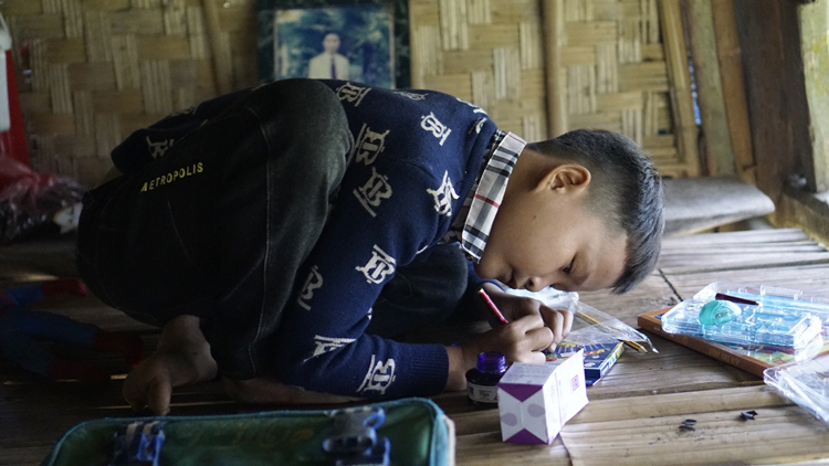 Khuyen sits on the floor to study. Photo by VnExpress/Trong Nghia.