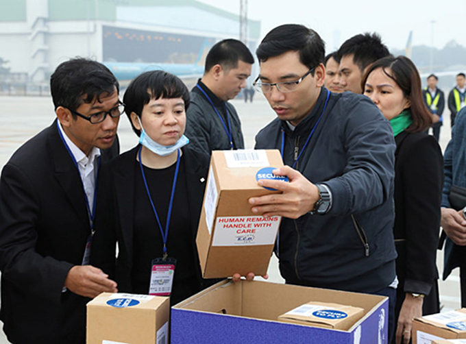 Officials inspect boxes of ashes of the U.K. truck victims at Noi Bai airport, Hanoi, November 30, 2019. Photo by Vietnam News Agency.