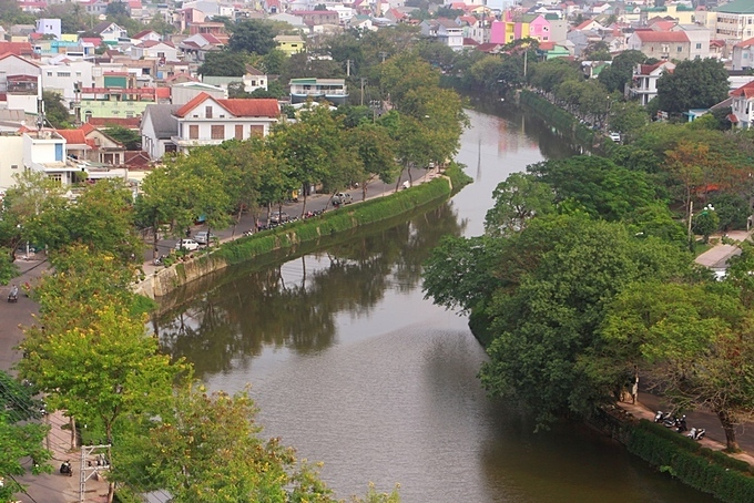 Phan Chu Trinh and Phan Dinh Phung Streets on the banks of An Cuu River create shade with green trees along both sides.