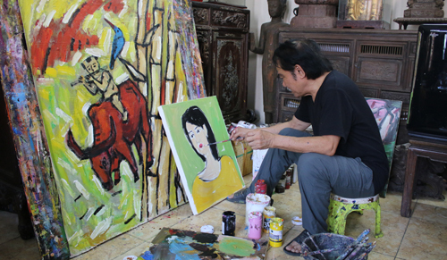 Pham Luc draws at his house. Photo by VnExpress/Hong Hieu.