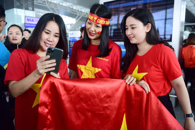 Three women are spotted with the Vietnamese flag and taking photos while waiting to be checked-in.