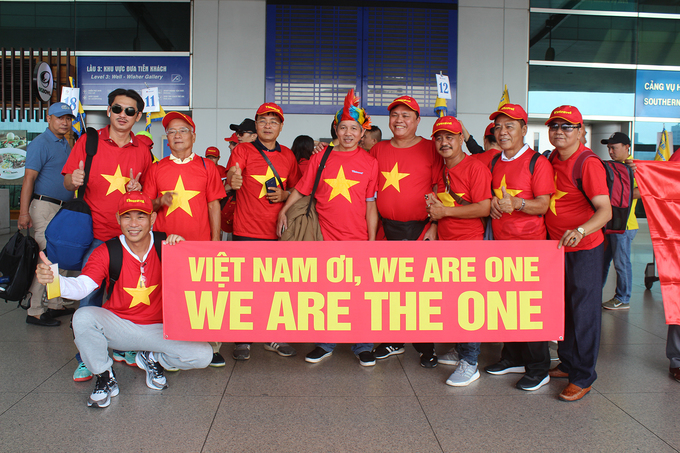A group of Vietnamese fans pose for a group picture, sporting a banner to cheer for the national team.