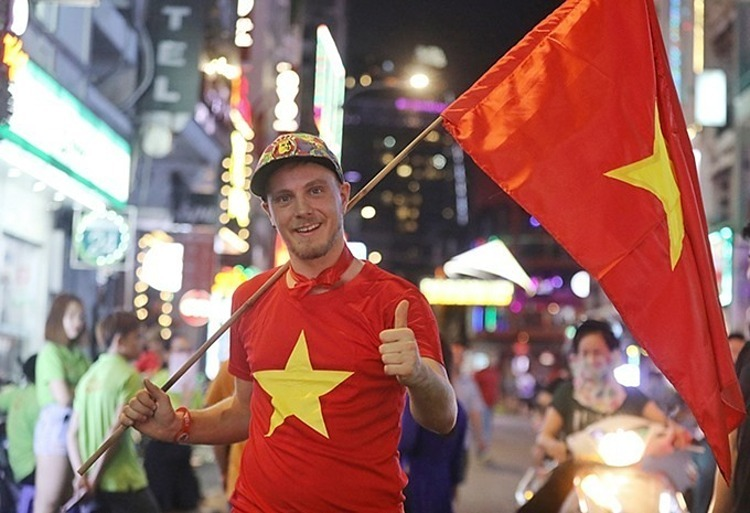 Ecleland, an American tourist, is supporting Vietnam on Bui Vien Street, a backpacker hangout in HCMC. Photo by VnExpress/Quynh Tran.