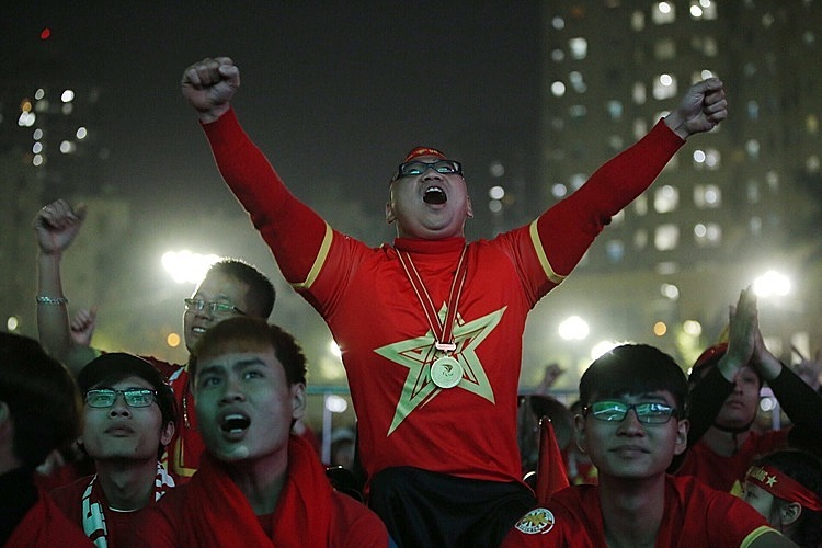 A fan leaps for joy in Hanois Hoan Kiem District after Vietnam scores the first goal in the SEA Games final against Indonesia. Photo by VnExpress/Dinh Tung.