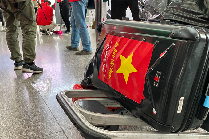 A sticker mimicking the Vietnamese flag is spotted on a suitcase.