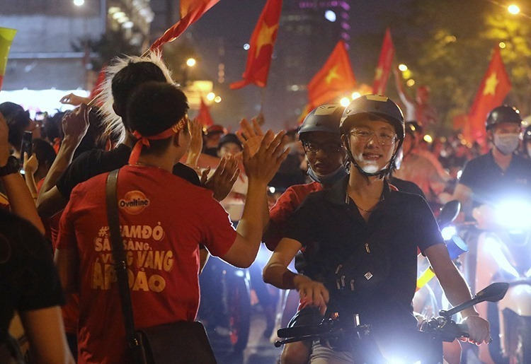 Fans share high five as they storm Ton Duc Thang Street in HCMCs District 1 on opposite sides. Photo by VnExpress/Quynh Tran.Fans burn flares to celebrate Vietnamese footballs historic victory on Xa Dan Street in Hanois Dong Da District. Photo by VnExpress/Minh Hai.